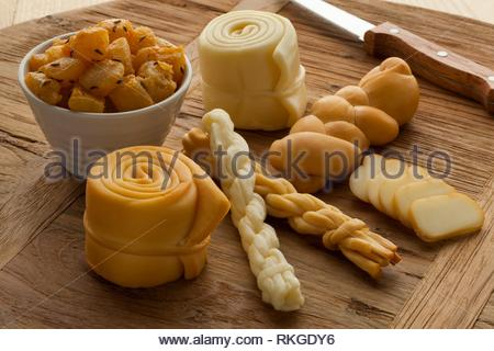 Different traditional smoked and unsmoked Slovakian cheeses on a wooden board. - Stock Photo