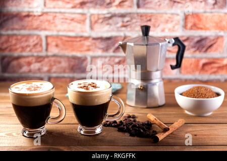 two cup of coffee, Italian coffee maker, coffee beans, cinnamon, napkin and brown sugar bowl on wood table and brick background. - Stock Photo