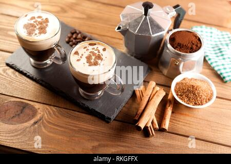 two cup of coffee, Italian coffee maker, coffee beans, cinnamon, napkin and brown sugar bowl on wood table. - Stock Photo