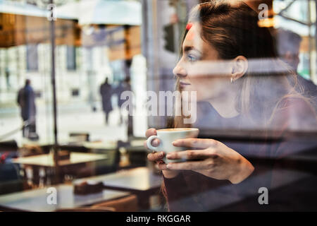 Girl daydreaming while holds a coffee cup at local coffee shop, concept photo through window for city effect with reflection