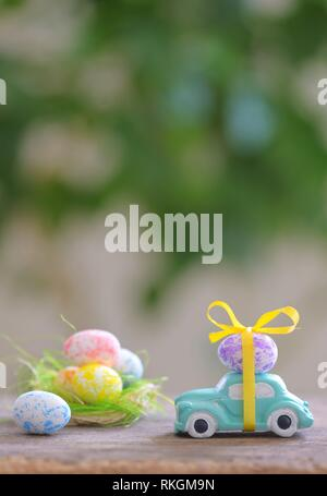 Toy car carrying easter egg in spring time. - Stock Photo