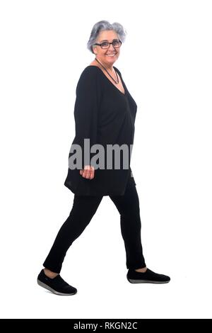 full portrait of a senir woman walking on white. - Stock Photo