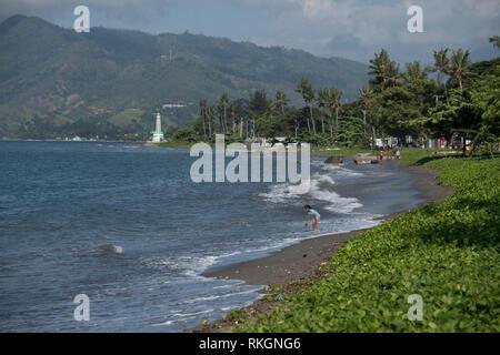 Beach, Girl with lighthouse in background, Dili, East Timor (Timor Leste) - Stock Photo
