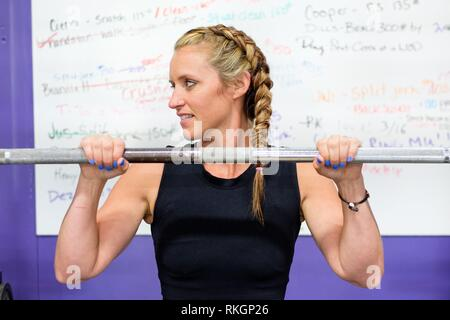 Portrait of a fit young woman at a crossfit gym for female athletes. - Stock Photo