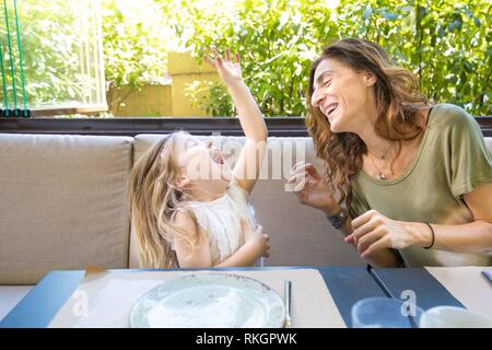 happy family in restaurant: woman mother and her daughter four years old blonde girl laughing out loud with funny face expression. - Stock Photo