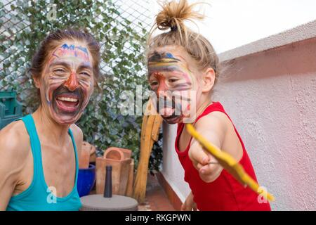 portrait of happy family with painted faces in party at terrace of house, three years old child sticking out tongue next to woman laughing. - Stock Photo