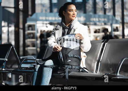 Young beautiful girl looking for something and rummaging in backpack. - Stock Photo