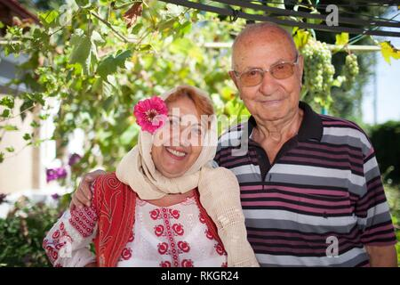 Romanian elder couple, the woman dressed in Romanian traditional folk costume. - Stock Photo