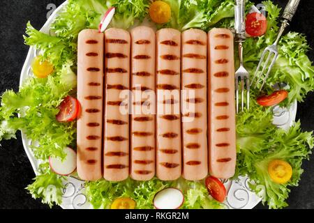 Plate with grilled Vienna sausage on fresh lettuce, tomatoes and radish salad, above shot. - Stock Photo