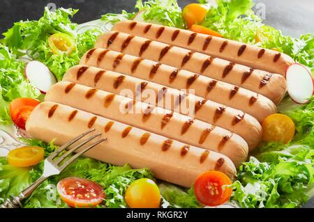Plate with grilled wurstel on fresh lettuce, tomatoes and radish salad. - Stock Photo