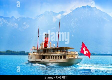 Geneve Lake Leman Geneva paddle steamer ship Switzerland with Swiss flag. - Stock Photo