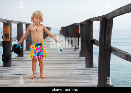 Happy little child with snorkeling mask, fins going to dive in tropical sea to exploring underwater nature. Travel lifestyle, water sports, swimming - Stock Photo