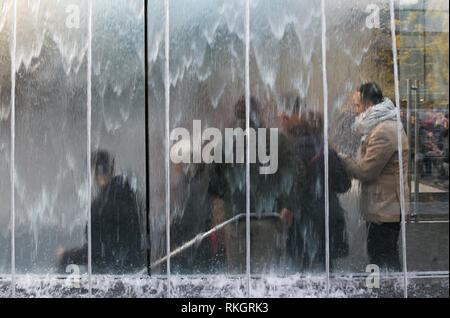 customers behind the glass fountain entering Apple store in Milan, Italy - Stock Photo