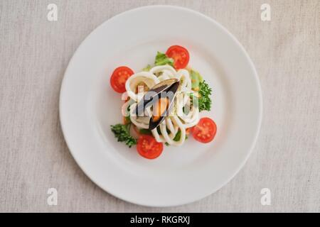 Squids and mussels with vegetables on a white plate on a white background with a shadow, top view. - Stock Photo