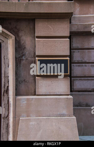 Blank brass plaque on stone building wall - Stock Photo