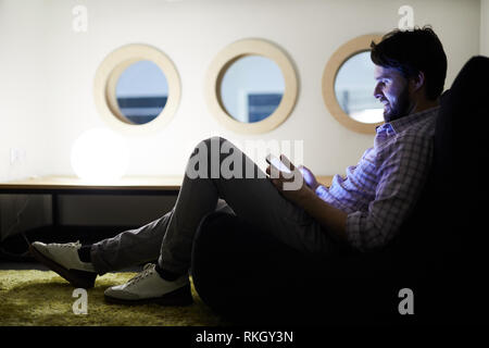 Young man surfing net on phone in dark room - Stock Photo