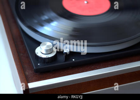 Old vintage turntable in wooden case with installed long play record with focus on speed rotation switch side view closeup - Stock Photo