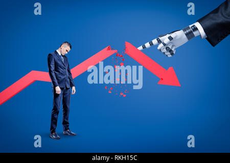 A sad businessman looking down with a broken red arrow behind and a big robotic hand in suit pointing at him. - Stock Photo