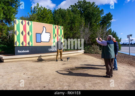 February 10, 2019 Menlo Park / CA / USA - Group of people taking photos with the Facebook logo (customized for black history month) - Stock Photo