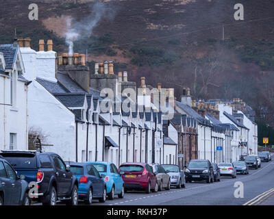 Parked cars and terraced houses in Shore Street on the waterfront at Ullapool, Highland, Scotland - Stock Photo