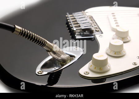 Part of modern electric six string guitar black color with glossy finish with metal jack in socket, pickups and control knobs isolated on white backgr - Stock Photo