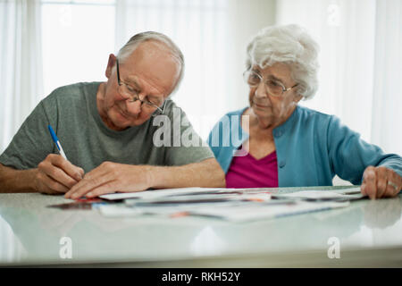 Anxious elderly couple sign some paperwork while they work through their big pile of bills. - Stock Photo