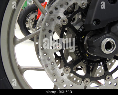 Brake disc on the front wheel of sport motorcycle at moto shop stock photo - Stock Photo