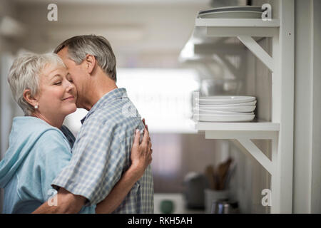 Affectionate mature couple tenderly embrace in the kitchen. - Stock Photo