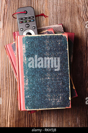 Stack a few books on wooden table with bookmark in shape of tv remote inserted in one book - Stock Photo