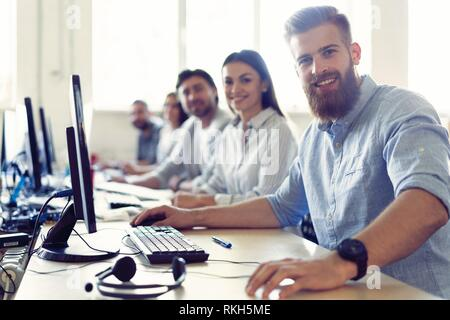 Colleagues are concentrated on their work, finding the solutions of their company problems, sitting at work places in a row in light modern office. - Stock Photo