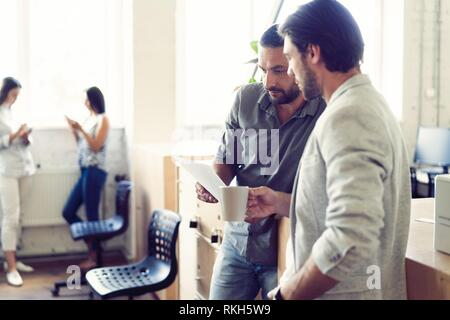 Nice coffee break. Two cheerful young people holding coffee cups and talking while standing in office. - Stock Photo