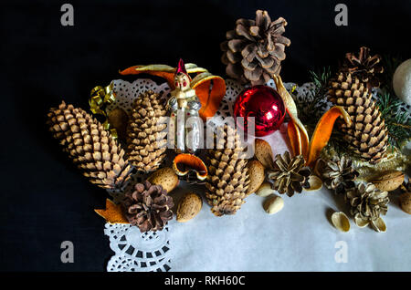 The edge of the paper napkin paper with various pine cones, pine twig, old worn Christmas decorations, almonds and orange peel on a black background - Stock Photo
