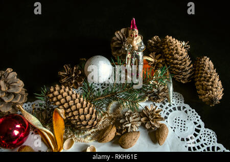 Corner of paper openwork napkin with various coniferous cones, a coniferous twig, old worn Christmas toys, almonds and orange peels on a black backgro - Stock Photo