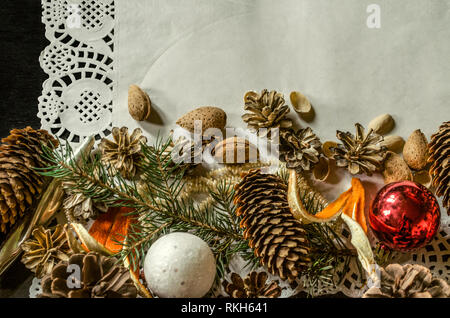 The bottom edge of the openwork paper napkin with various pine cones, fir branch, old worn Christmas toys, almonds and orange peel on a black backgrou - Stock Photo