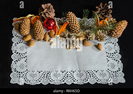 Square openwork paper napkin with various pine cones, spruce branch, old worn Christmas tree toys, almonds and orange peel on black background - Stock Photo