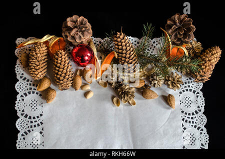 The top half of an openwork paper napkin with various cones, a fir branch, old worn Christmas toys,almonds and orange peel on a black background - Stock Photo