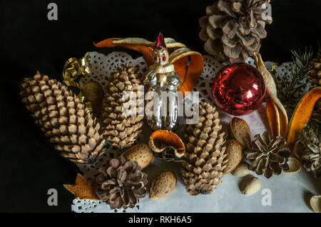 The openwork paper napkin with various pine cones, fir branch, old worn Christmas toys, almonds and orange peel on a black background - Stock Photo