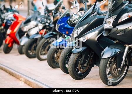 Motorbike, motorcycle scooters parked in row in city street. Close up of wheel. - Stock Photo