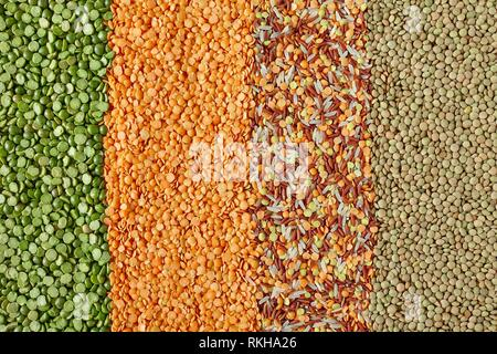 Dried legumes in vertical layers, from left to right: green split peas, red lentils, mix of red Thai rice, white Thai perfume rice, red and yellow - Stock Photo