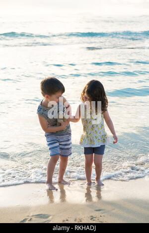 Siblings experiencing the beach and ocean together while on a tropical vacation to Oahu Hawaii with nice warm weather even at sunrise. - Stock Photo