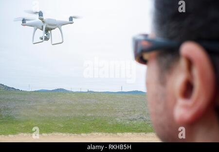 Pilot flying drone a cloudy day on countryside. Aproaching maneuver. - Stock Photo