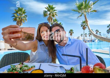 Young couple selfie smartphone photo in a swimming pool restaurant. - Stock Photo