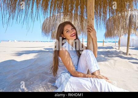 young latin woman in a beach under parasol at summer. - Stock Photo
