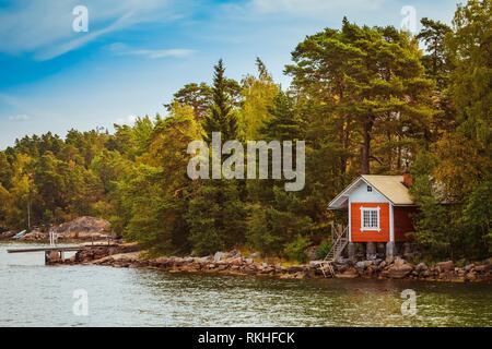 Red Finnish Wooden Sauna Log Cabin On Island In Autumn. - Stock Photo