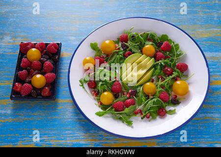 Avocado and berries salad with arugula and yellow cherry tomatoes. - Stock Photo
