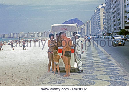 Copacabana beach with a street vendor selling soft drinks, Rio de Janeiro, Brazil, c. 1960. Copacabana is a bairro (neighbourhood) located in the southern part of the city. It is famous for its 4 km (2.5 miles) Balneario Beach, one of the best-known in the world. - Stock Photo