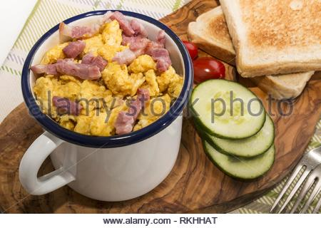 scrambled eggs with roasted bacon in an enamel mug, served with toasted slice of bread, cucumber slices and plum tomatoes on wooden board. - Stock Photo