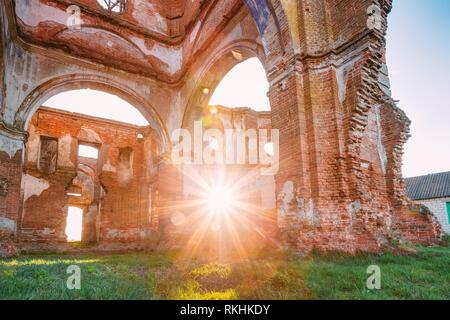 Sun Shines Through The Red Brick Walls Of Old Ruined Orthodox Church Of The St. Nicholas In Village Lenino, Dobrush District, Gomel Region, Belarus. - Stock Photo