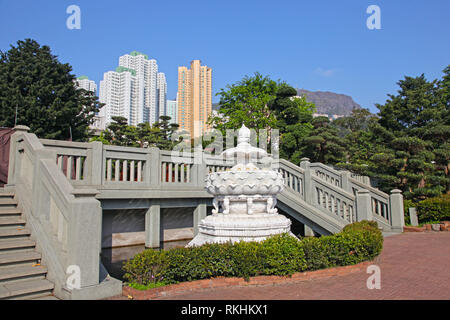 White lotus flower fountain in Nan Lian Garden near Chi Lin Nunnery with city skyscrappers in the background, Hong Kong . - Stock Photo