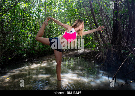 Young woman practicing yoga (Lord of the Dance Pose -  Natarajasana) in a natural setting - Fort Lauderdale, Florida, USA - Stock Photo